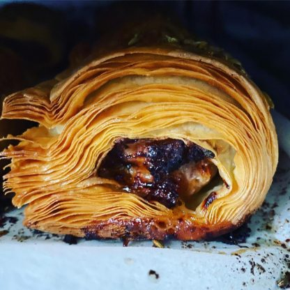 A side-on view of a pork & fennel sausage roll